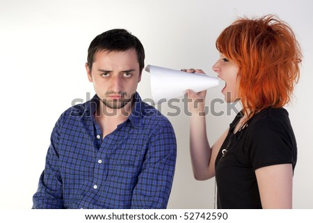 Girl shouting in a megaphone at young man