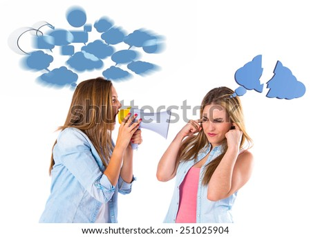 Girl shouting with a megaphone at her friend - stock photo