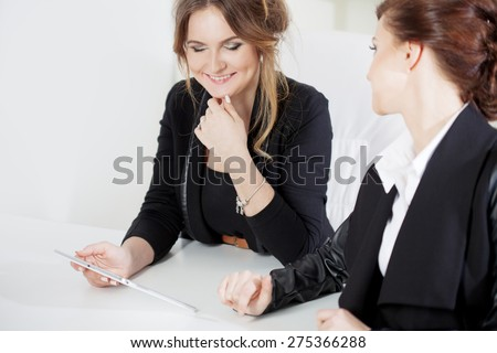 Girl showing something to her colleague, work in the office - stock photo