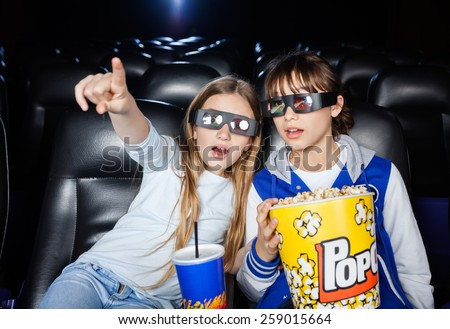 Girl showing something to sister while having snacks at 3D cinema theater - stock photo