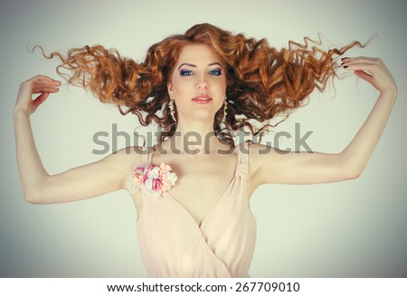 girl shows her beautiful hair. cheerful girl holding her beautiful hair curly.Girl throws up his red hair - stock photo