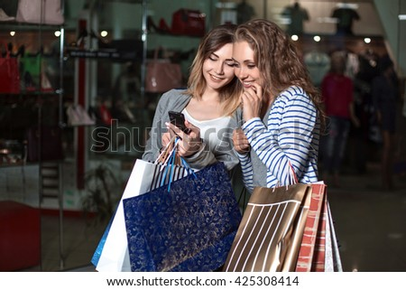 girl shows on a mobile phone is something his girlfriend. Fashion Shopping two ladies Portrait. Beauty Woman with Shopping Bags in Shopping Mall. Shopper. Sales. Shopping Center