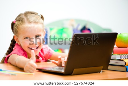 Girl Shows thumb at the laptop - stock photo