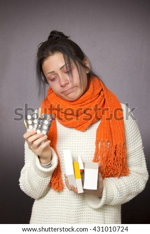 girl sick with the flu with tablets in hands on dark background