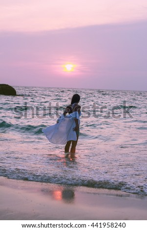 Girl silhouette watching sunset at ocean - stock photo
