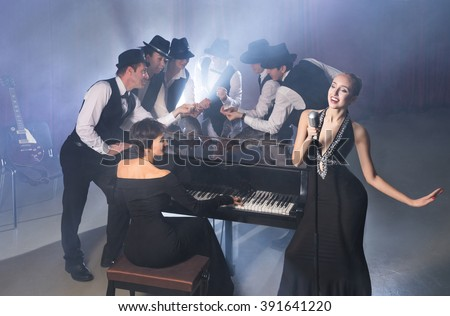 Girl singing into retro microphone to the accompaniment of the piano and the guitar and back-vocals
