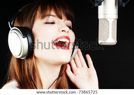 girl singing to the microphone in a studio - stock photo