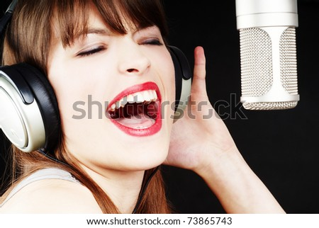girl singing to the microphone in a studio
