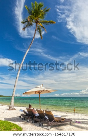 Girl sit at beach Lounge chairs under palm tree leaves at the shore of Indian ocean, Zanzibar, Tanzania