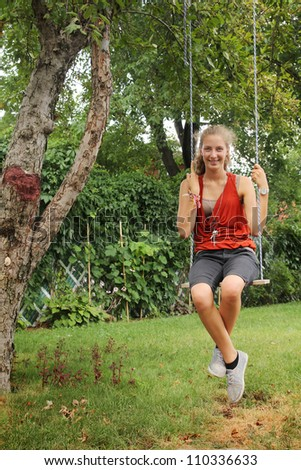 Girl sit on a swing outside in a garden