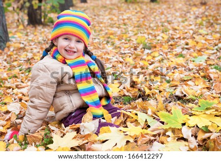 girl sit on yellow leaves in autumn park