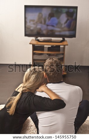 girl sits and rests on a strong sholder for a Man on the floor on TV background - couple embracing with each other - stock photo