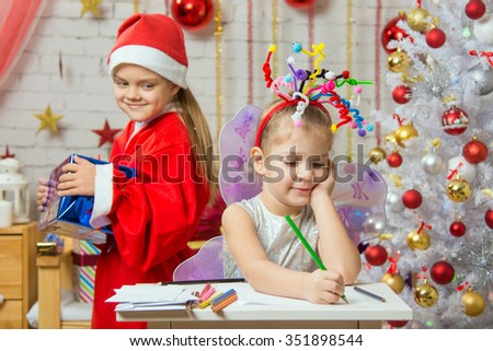 Girl sits at a table with fireworks on the head, Santa Claus brings her Christmas gift