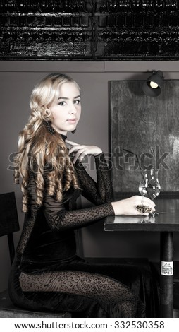 Girl sits at table in night club with glass filled with drinking water .