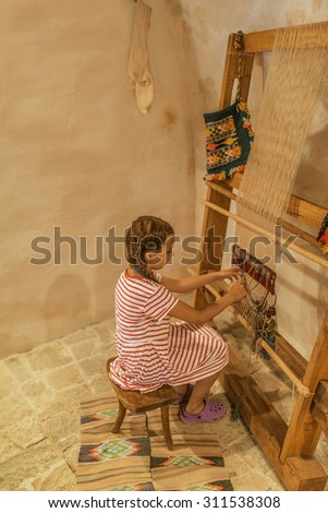 Girl sits at the old loom in the ancient house. - stock photo