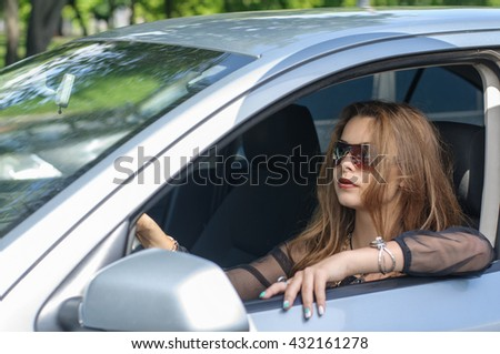 Girl sits in a car as a driver. Concept: transport, lifestyle, business - stock photo