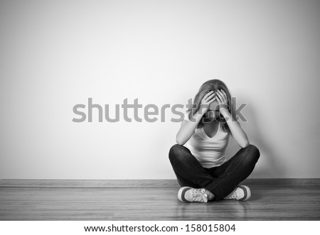 girl sits in a depression on the floor near the wall monochrome - stock photo