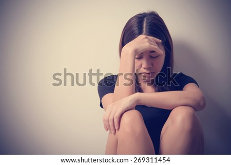 girl sits in a depression on the floor near the wall with vintage filter effect  - stock photo