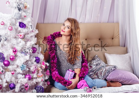 Girl sits on a couch near the Christmas tree. New Year. Waiting for a miracle. Merry Christmas. Home comfort. Girl lays out gifts. Model Posing. - stock photo