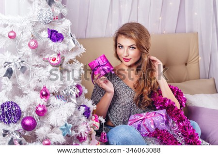 Girl sits on a sofa near the Christmas tree. New Year. Waiting for a miracle. Merry Christmas. Home comfort. Girl lays out gifts. - stock photo