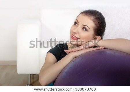 Girl sits on the floor after exercising near a gymnastic ball. Concept: lifestyle, fitness, aerobics and health.
