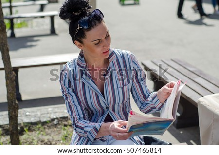 girl sittin on the bench in the park and reading journal