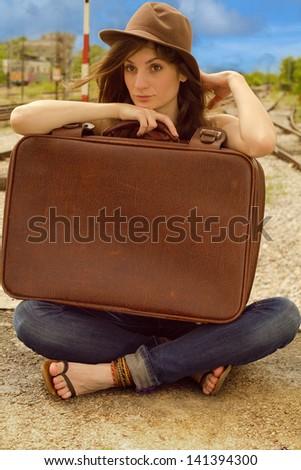 Girl sitting and holding an old suitcase - stock photo