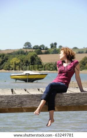 Girl sitting and sunbathing on landing stage in brittany - stock photo
