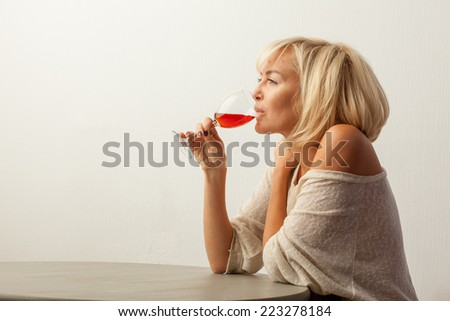 Girl sitting at a table with a wine glass - stock photo