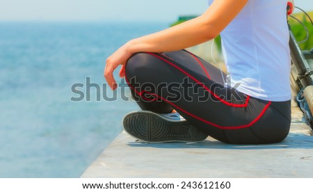 Girl sitting at seaside and relaxing, woman fitness, healthy lifestyle
