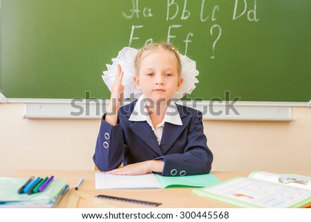 Girl sitting at the desk at school, on the background of the board, where she wrote the english alphabet. Schoolgirl raised her hand up. On the table lay a notebook, pen, pencil. - stock photo