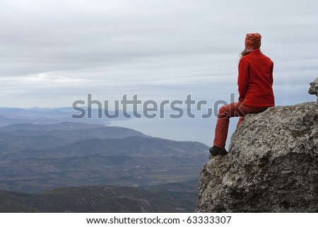 girl sitting at the edge of rock - stock photo