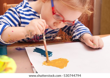 girl sitting at the table and draws paints on white paper