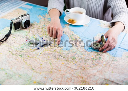 girl sitting at the table with a card camera, a compass and a plane and travel plans. Desired time holidays - stock photo