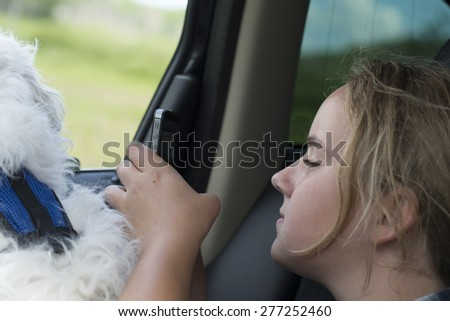 Girl sitting in a car using a mobile phone, Lake Audy Campground, Riding Mountain National Park, Manitoba, Canada - stock photo