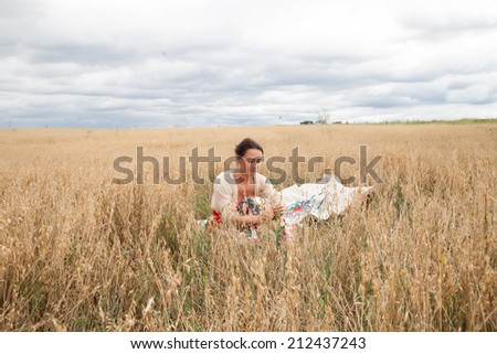Girl sitting in a field of wheat ears