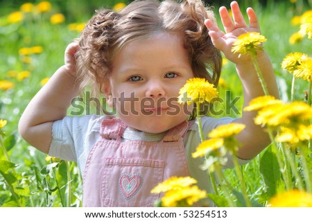 Girl sitting in a meadow with their hands up