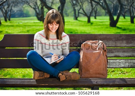girl sitting in a park and doing her homework - stock photo