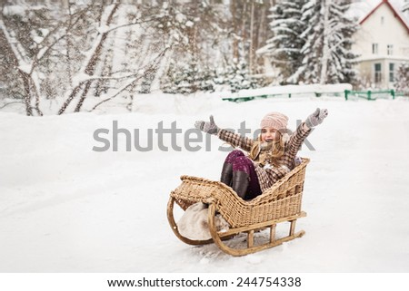Girl sitting in a vintage wooden sled and joyfully throwing their hands. In Winter - stock photo