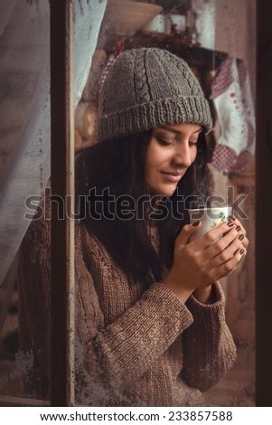 Girl Sitting In A Window Near The Fireplace Drinking Tea Or Coffee - stock photo