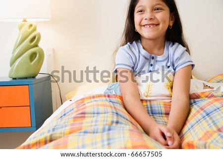 Girl sitting in bed - stock photo