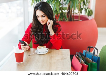 Girl sitting in cafe in shopping mall with cup of coffee, looking at phone. Her hand near chin. Colorful shopping bags standing near her. Holding phone. Wearing red blouse. Indoor, waist up - stock photo