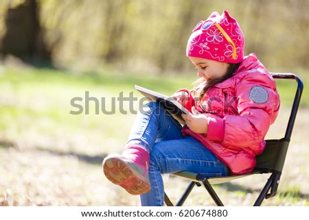 Girl sitting in garden on chair holding tablet