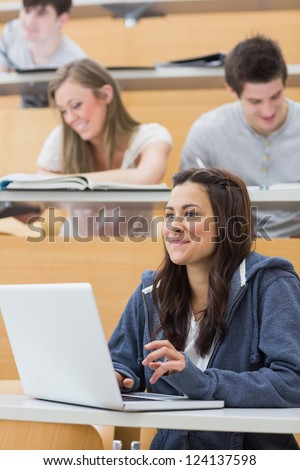 Girl sitting in lecture hall using laptop and smiling