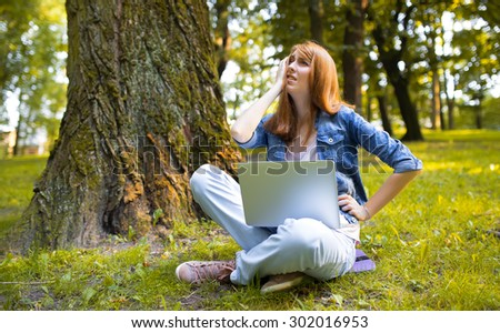 Girl sitting in park and working on her laptop.