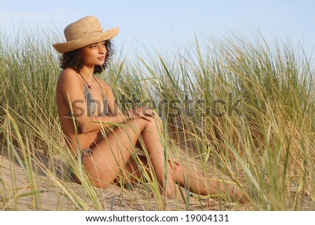 Girl sitting in sand dunes looking thoughtful