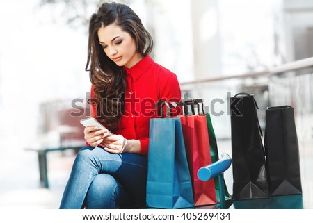 Girl sitting in shopping mall, looking at phone. Beautiful girl holding phone in hands and colorful shopping bags lying near her. Leg put on other leg. Wearing red blouse and jeans. Nice make up. - stock photo