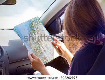 girl sitting in the car looking map - stock photo
