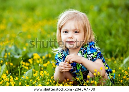girl sitting in the grass and yellow flowers on his haunches