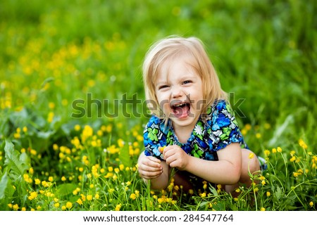 girl sitting in the grass and yellow flowers on his haunches and laughs - stock photo